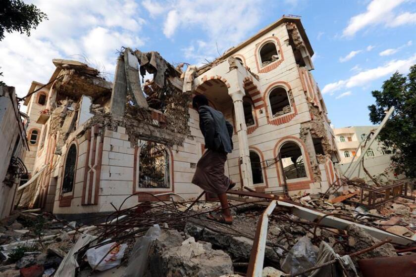 Un yemení camina junto a los escombros de un edificio destruido tras un supuesto ataque de la coalición liderada por Arabia Saudí, en Saná (Yemen). EFE/Archivo