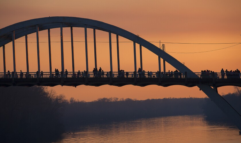 People walk and stop along the Edmund Pettus Bridge at dusk March 2015 in Selma.