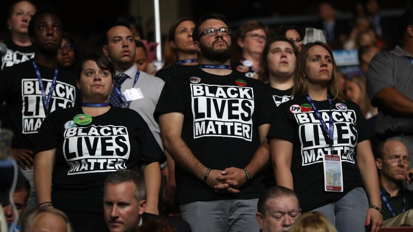 Supporters of the Black Lives Matter movement stand during remarks from the Mothers of the Movement on the second day of the Democratic National Convention.
