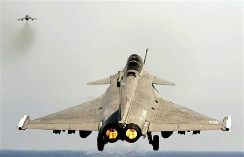 FILE- In this March 29, 2011 file photo provided by the French Army, a Rafale jet fighter takes off from the flight deck of the Charles de Gaulle aircraft carrier in the Mediterranean sea, as part of the Operation Odyssey Dawn. In recent weeks, India has decided to buy 126 fighter jets from France, taken delivery of a nuclear-powered submarine from Russia and worked to ready its first aircraft carrier modernizing its military to face a rising China. (AP Photo/Marine Nationale, Cyril Davesne, File) NO SALES