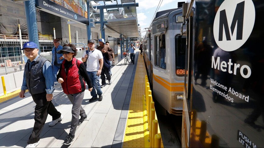 Commuters disembark from the Expo Line at the downtown Santa Monica station, which opened to service in May.