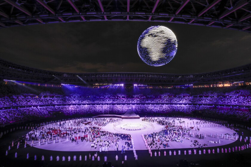 Lighted drones form the shape of a spinning earth over a crowd of people on the floor of the Olympic Stadium in Tokyo.