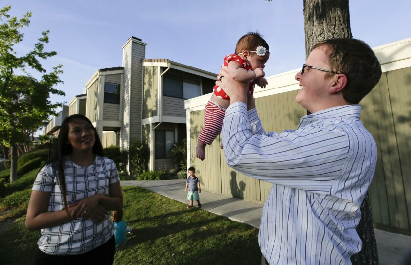 HOLD FOR BUSINESS STORY MOVING TUESDAY 5/12 : Brett Singley, right, poses for a picture in front of their condo with his wife Angelynn 28, and their children, Ben 2, Isla 5, Aria 1 month, and Isaiah 3, on Monday, May 11, 2015 in Santa Clarita, Calif. Singley, a first-time buyer in Los Angeles and a father of four, knew the kind of house he wanted and how much he could afford. But after six months of searching, the civil engineer shifted his sights to smaller and less expensive townhomes. Last month, he bought one in Santa Clarita. (AP Photo/Chris Carlson)