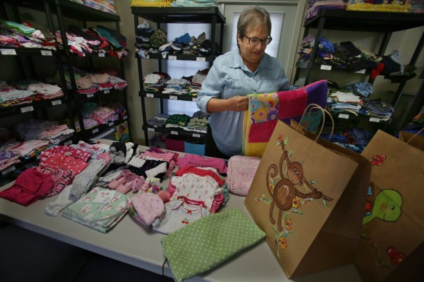 Judi Lawson, a volunteer, fills one of the bags with a year's worth of clothes for a newborn, and a newly made quilt donated by other volunteers
