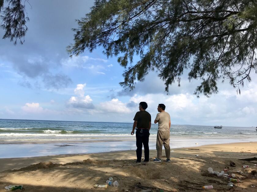 Two Chinese nationals stand on the litter strewn Otres Beach in Sihanoukville, Cambodia. An influx of Chinese investors has transformed the once sleepy coastal city, but a deadly June 22 building collapse has renewed questions about the quality of Chinese construction and the Cambodian government's close ties to Beijing