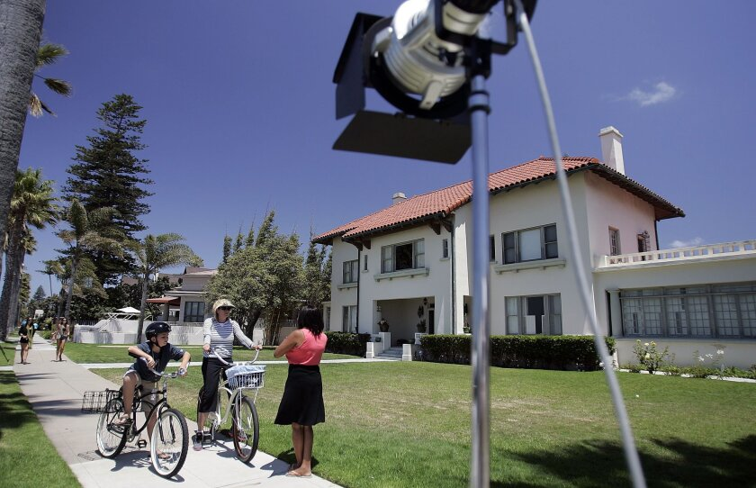 A local television reporter talks to members of the public in front of the Spreckels mansion on Ocean Boulevard.