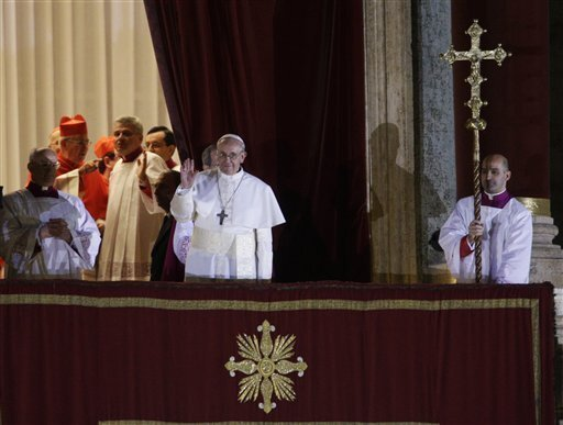 Pope Francis flanked by Monsignor Guido Marini, master of liturgical ceremonies, waves to the crowd from the central balcony of St. Peter's Basilica at the Vatican, Wednesday, March 13, 2013. Cardinal Jorge Bergoglio, who chose the name of Francis is the 266th pontiff of the Roman Catholic Church.