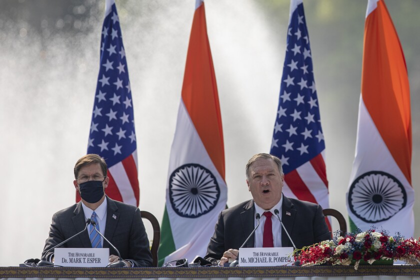U.S. Secretary of State Mike Pompeo, right, speaks with Secretary of Defence Mark Esper seated beside him during a joint press conference with their Indian counterparts at Hyderabad House in New Delhi, India, Tuesday, Oct. 27, 2020. With President Donald Trump in a tight race for a second term against former Vice President Joe Biden, Pompeo and Esper sought to play on Indian suspicions about China to shore up a regional front against increasing Chinese assertiveness in the Indo-Pacific region. (AP Photo/Altaf Qadri)