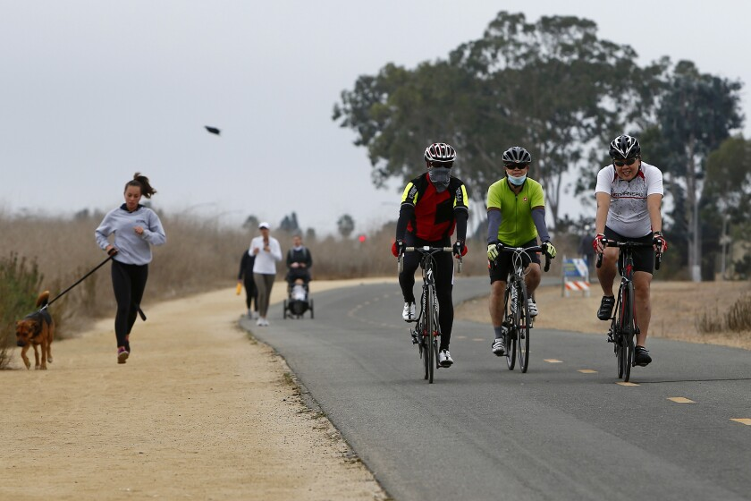 Cyclists cruise along a path at Upper Newport Bay in Newport Beach.