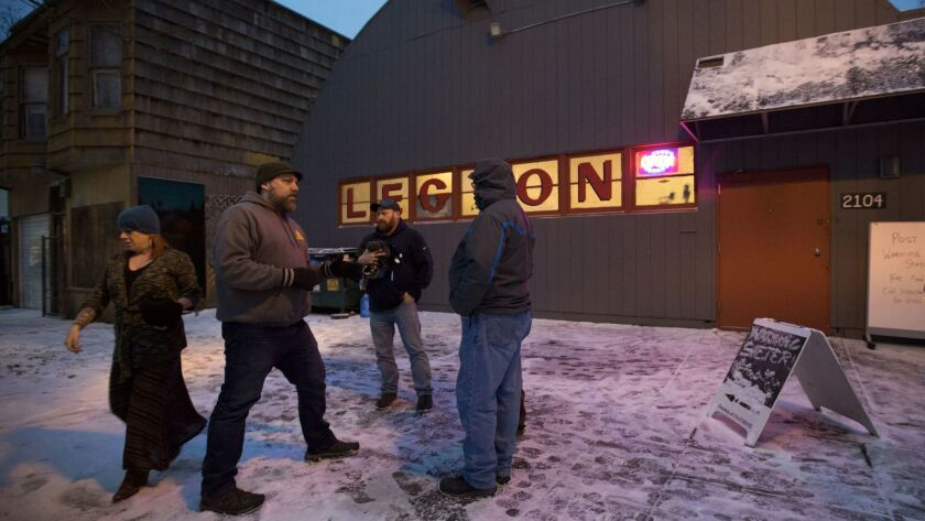 Sean Davis, second from left, commander of American Legion Post 134 in Portland, Ore., coordinates with other veterans to open the facility as a shelter during a recent cold spell.