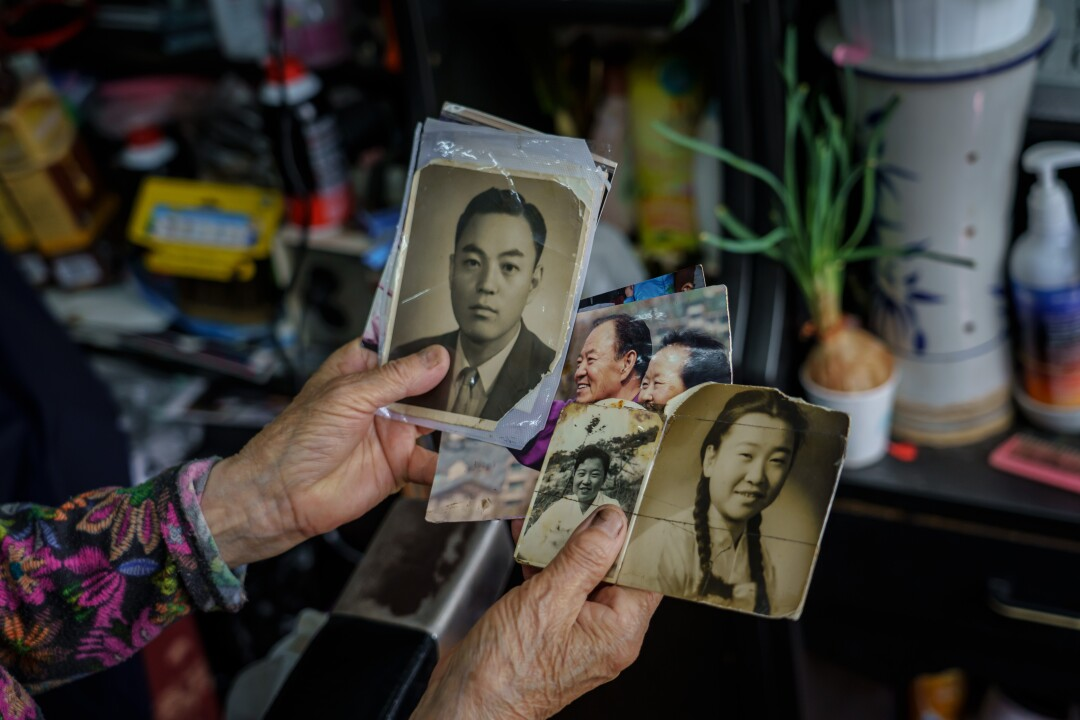 Barber Lee Duk-hoon shows old family photographs at her shop in Seoul