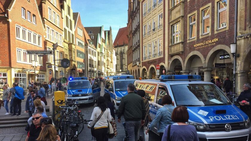 People walk past police cars in Muenster, Germany, where several people were killed or injured when a car crashed into pedestrians on Saturday, April 7, 2018.