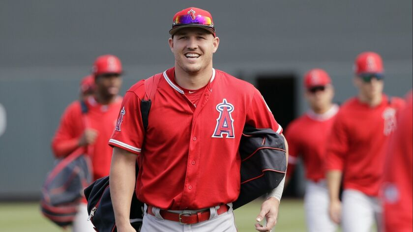 Angels center fielder Mike Trout smiles as he walks onto the field with teammates before a spring training baseball game against the Arizona Diamondbacks on Thursday.