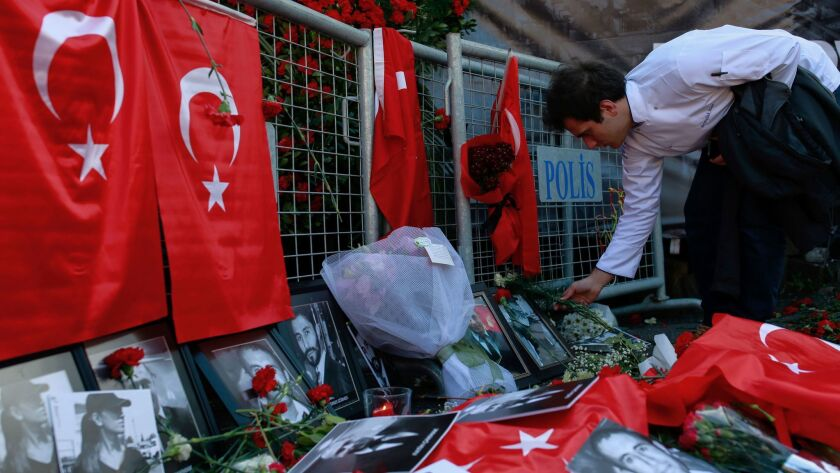 A man leaves carnations at the scene as people on Tuesday protest an attack at a popular nightclub in Istanbul.