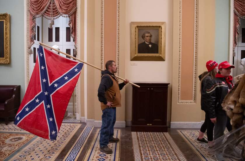 Kevin Seefried holds a Confederate flag outside the Senate Chamber after breaching the US Capitol.