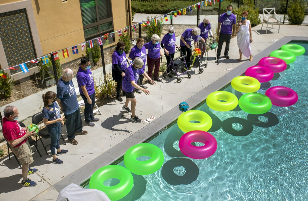 People, many in matching purple shirts, line a swimming pool filled with colorful flotation rings