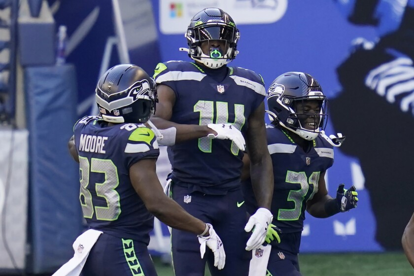 Seattle Seahawks wide receiver DK Metcalf (14) celebrates with teammates David Moore, left, and DeeJay Dallas, right, after Metcalf scored a touchdown against the San Francisco 49ers during the first half of an NFL football game, Sunday, Nov. 1, 2020, in Seattle. (AP Photo/Elaine Thompson)