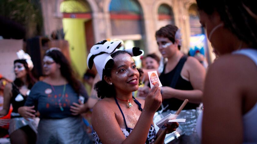 """In this Feb. 3, 2018 photo, a woman in a cow costume distributes stickers during the block party """"Ma"""