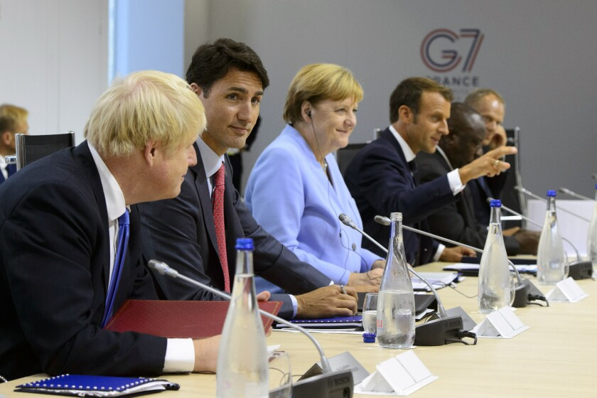 FILE - In this Aug. 26, 2019, file photo Canadian Prime Minister Justin Trudeau, second from left, sits between British Prime Minister Boris Johnson, left, and German Chancellor Angela Merkel as they take part in a meeting at the G7 Summit in Biarritz, France. Gesturing at right is French President Emmanuel Macron. It's a very exclusive club, perhaps the most selective in the world. Its current board members are Angela, Boris, Emmanuel, Justin, Mario, Yoshihide, and relative newcomer Joe. And they will be meeting this week after four years of U.S. disruption and a two-year coronavirus interruption. (Sean Kilpatrick/The Canadian Press via AP, File)