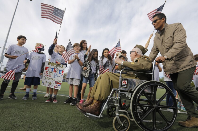 in this file photo, Joe Reilly, 96, a World War II veteran is pushed by Donnie Edwards.
