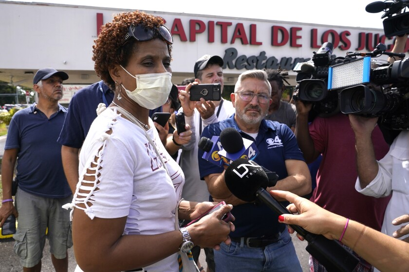 A woman talks with the news media near the scene of a shooting