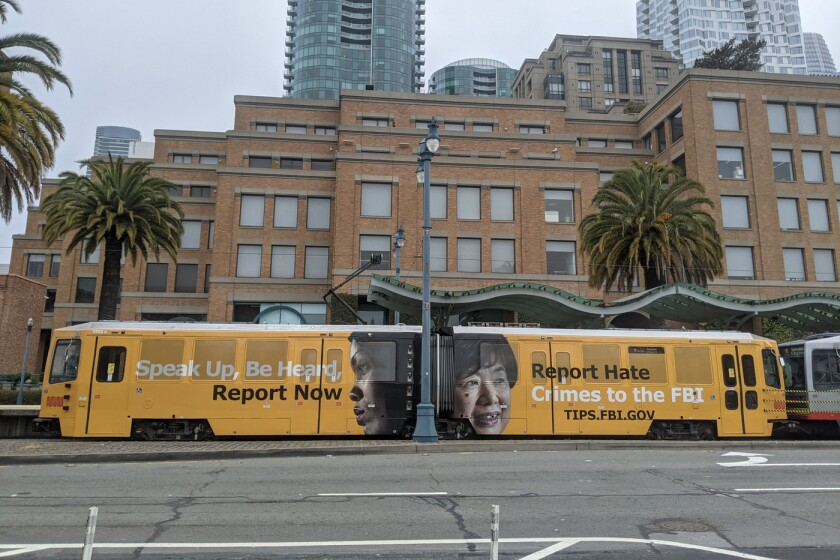 """In this image provided by the FBI, an ad on a San Francisco city train reads """"Speak Up, Be Heard, Report Now. Report Hate Crimes to the FBI."""" as part of a publicity campaign by the San Francisco FBI office to encourage victims of hate crimes to come forward and report hate incidents, federal officials announced Thursday, May 6, 2021. It also launched a social media campaign that includes the photo of an elderly Asian woman and a message that reads, """"Did you know many hate crimes are not reported? The FBI wants to help but we need to hear from you."""" (FBI via AP)"""