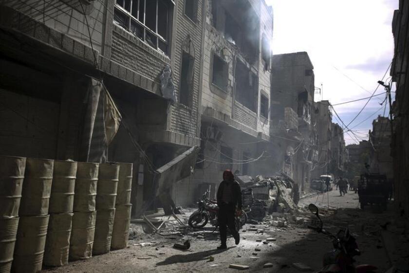 Fotografía de archivo de un hombre caminando entre los escombros tras un ataque aéreo supuestamente cometido por fuerzas aliadas. EFE/Archivo