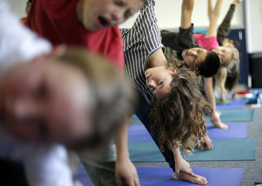 FILE - In this Dec. 11, 2012 file photo, students hold their position during a yoga class at Capri Elementary School in Encinitas, Calif. A California appeals court says yoga taught in San Diego County schools doesn't violate religious freedom. (AP Photo/Gregory Bull, File)