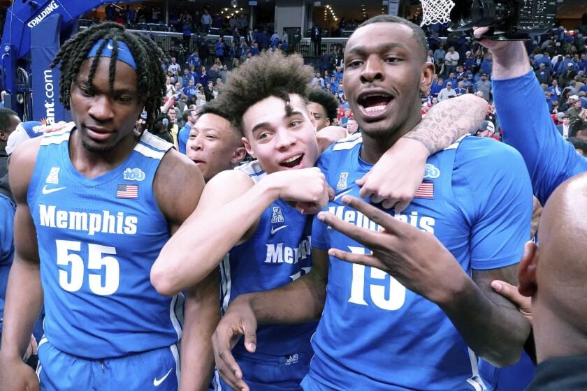Memphis Tigers Precious Achiuwa (55), Lester Quinones (11) and Lance Thomas (15) celebrate after a win against Houston in an NCAA college basketball game Saturday, Feb. 22, 2020, in Memphis, Tenn. (AP Photo/Karen Pulfer Focht)
