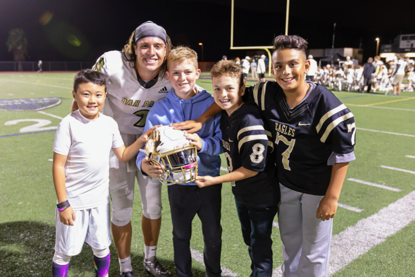 Oak Park quarterback/kicker Gianni Smith poses for a picture with some of his fans.