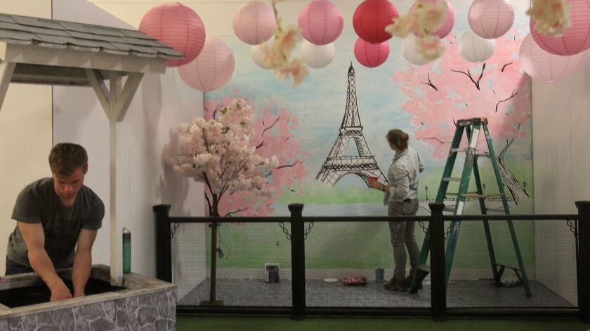 Muralist Hanna Daly paints a Paris scene as Ryan Erpelding works on a wishing well Thursday for the