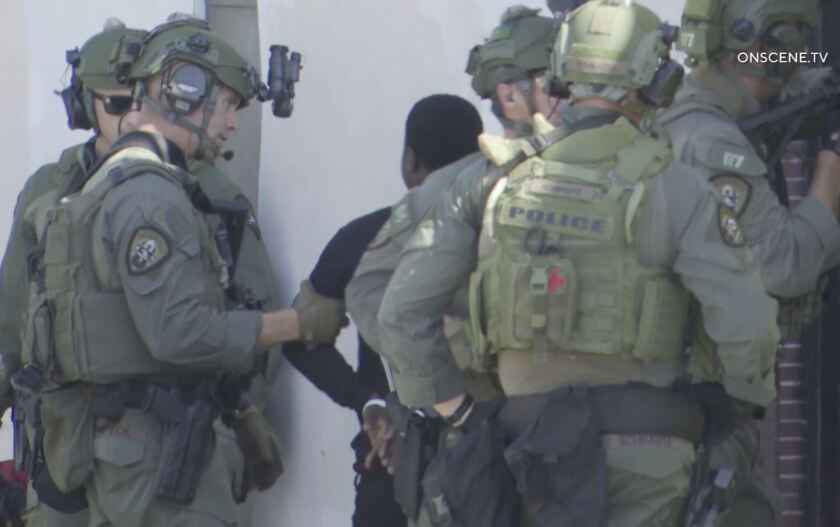 San Diego police SWAT officers take a young man into custody Friday afternoon outside an apartment on University Avenue in City Heights.
