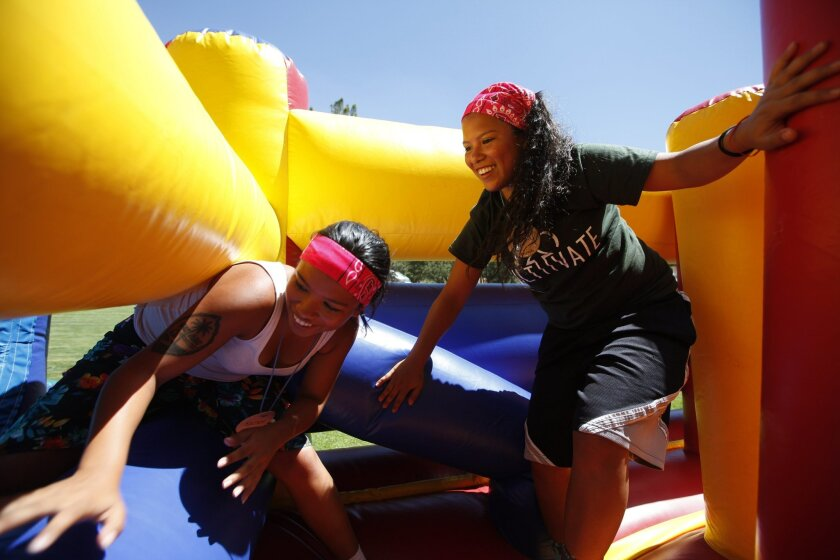 About 85 foster kids separated from their siblings had the opportunity to reconnect at a four day camp where they were able to participate in activities together. Sisters Rachel and Rosa scurry through an inflatable obstacle course together enjoying their time together.