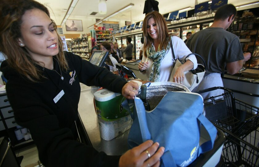 Cashier Julie Negron puts groceries in a reusable bag for customer Danielle Leopold of Leucadia on Friday at the Seaside Market in Cardiff-by-the-Sea. At the Seaside Market, even the shoppers who brought their own bags for carrying away their groceries weren't aware that Friday was the beginning of that city's ban on the distribution of single-use plastic bags. Shoppers who don't bring their own can opt to either get a paper bag for an extra 10 cents or purchase a reusable one, which, at Seaside Market, cost 99 cents. The ban initially affects grocery stores, mini-markets and liquor stores as well as retailers who sell groceries like Walmart.