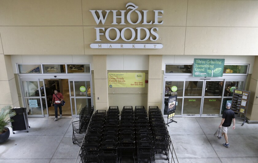 Amazon is adding curbside grocery pickup at Whole Foods for Prime members. Shoppers will be able to order groceries on the Prime Now app, park in a reserved parking space and a worker will place the groceries in their car.