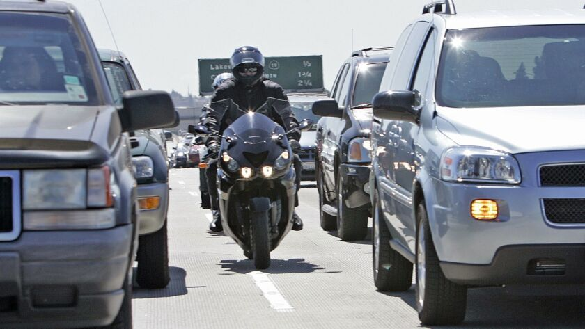 Motorcyclists drive between lanes of cars on the 405 Freeway in Long Beach in 2007.