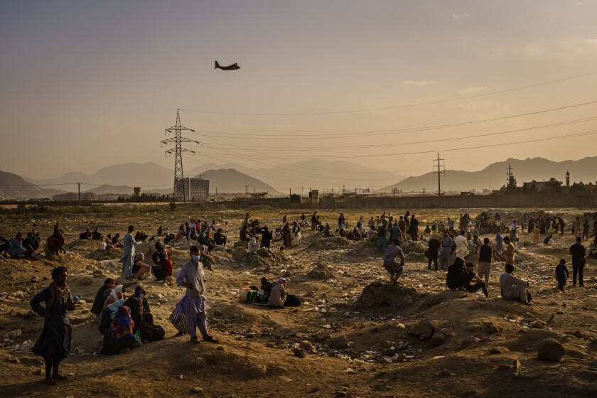 A military transport plane launches off while Afghans, who cannot get into the airport to evacuate, are stranded outside