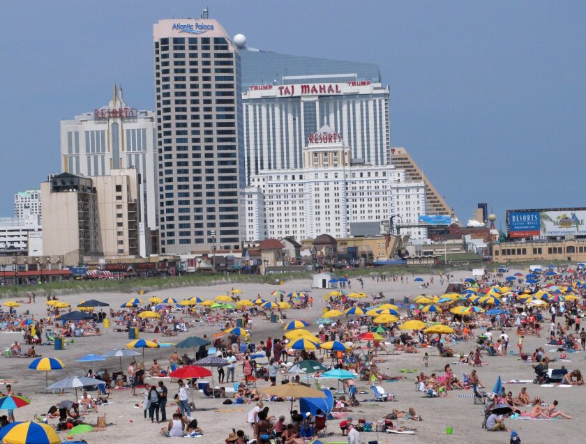 In this July 3, 2015 photo, beach goers sunbath in front of casinos in Atlantic City, N.J. If New Jersey follows through on its plans to allow two new casinos in the New York City suburbs, analysts and gambling industry officials agree they could be among the most successful in the country. But som