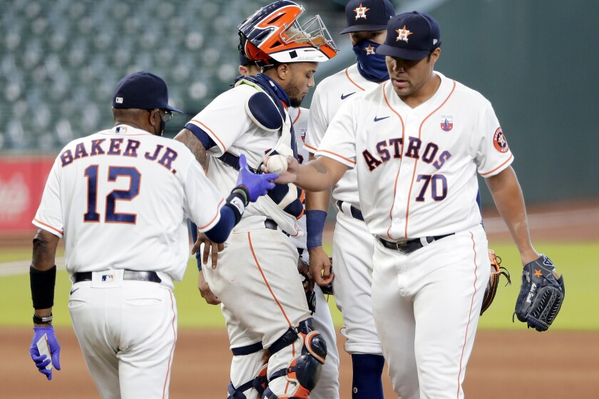 Houston Astros manager Dusty Baker Jr. (12) takes the ball from relief pitcher Andre Scrubb (70) as Scrubb is relieved during the seventh inning of a baseball game against the Seattle Mariners, Sunday, Aug. 16, 2020, in Houston. (AP Photo/Michael Wyke)