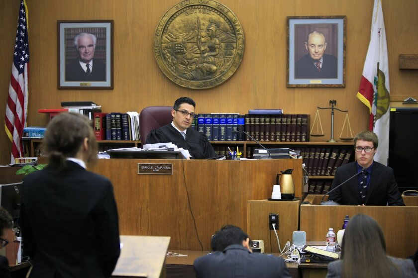 San Diego County Superior Court Judge Enrique Camarena listens as San Diego High School student Zeina Nemeh, as a defense attorney, asks Bonita Vista High student Matthew Moran, as a police officer, questions during the San Diego County High School Mock Trial Competition at the downtown courthouse.