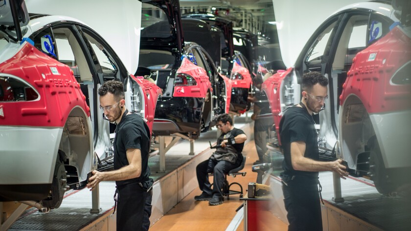 A worker is reflected in a computer screen as he and others assemble cars on the line at Tesla's factory in Fremont.
