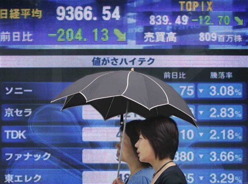 Women walk in front of an electronic stock board at a securities firm in Tokyo, Japan, Wednesday, June 30, 2010. Japan's benchmark Nikkei 225 stock average lost 204.13 points to end the morning session at 9366.54. (AP Photo/Itsuo Inouye)