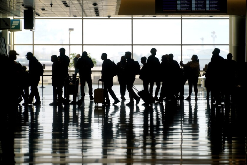 FILE - In this Wednesday, March 17, 2021 file photo, travelers walk through the Salt Lake City International Airport in Salt Lake City. Of the 2 million people clogging airport security lines and gate areas again each day, one crowd is still largely missing: business travelers. Their absence is noteworthy because they are a key source of revenue and profit, underpinning a record-breaking stretch of financial gain for U.S. airlines that ended with the coronavirus. Business travelers tend to pay higher fares, and that is especially true on international flights, which are also still deeply depressed by the pandemic and travel restrictions around the globe. (AP Photo/Rick Bowmer, file)