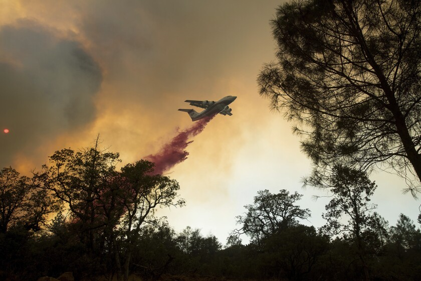 A plane drops retardant while battling a wildfire near Oroville.