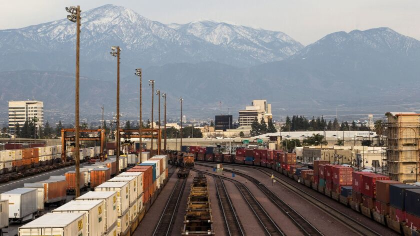 Snow-covered mountains loom in the background above the San Bernardino rail yard, which has some the the worst air quality in the area. A plan by Southern California air regulators would rely on voluntary measures from rail yards and ports to limit harmful emissions.