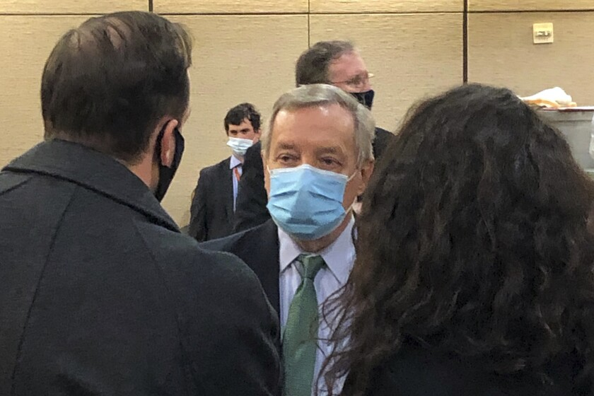 Sen. Dick Durbin, D-Ill., talks with reporters in a secret location on the U.S. Capitol complex where Senators were taken when the Senate was evacuated after protesters stormed the building on Wednesday, Jan. 6, 2021, in Washington. Associated Press reporter Andrew Taylor and other reporters were spirited away along with senators for safety for a few hours. When they returned to the Senate wing of the Capitol, it was crowded with police and security agents, and there was tear gas residue.(AP Photo/Andrew Taylor)