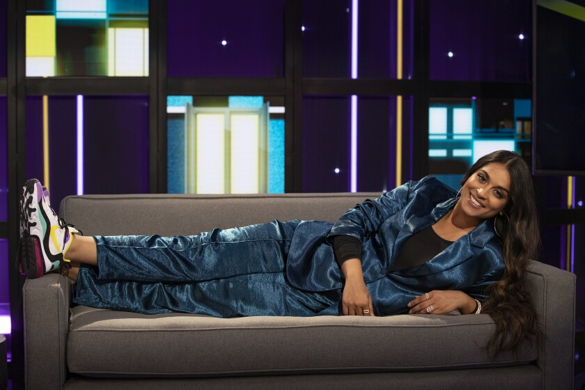 """Lilly Singh laying on the couch on the set of her new show, """"A Little Late"""""""