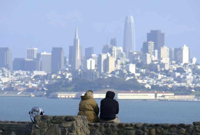 A couple view the San Francisco skyline from a vista point in Sausalito, Calif., in March.