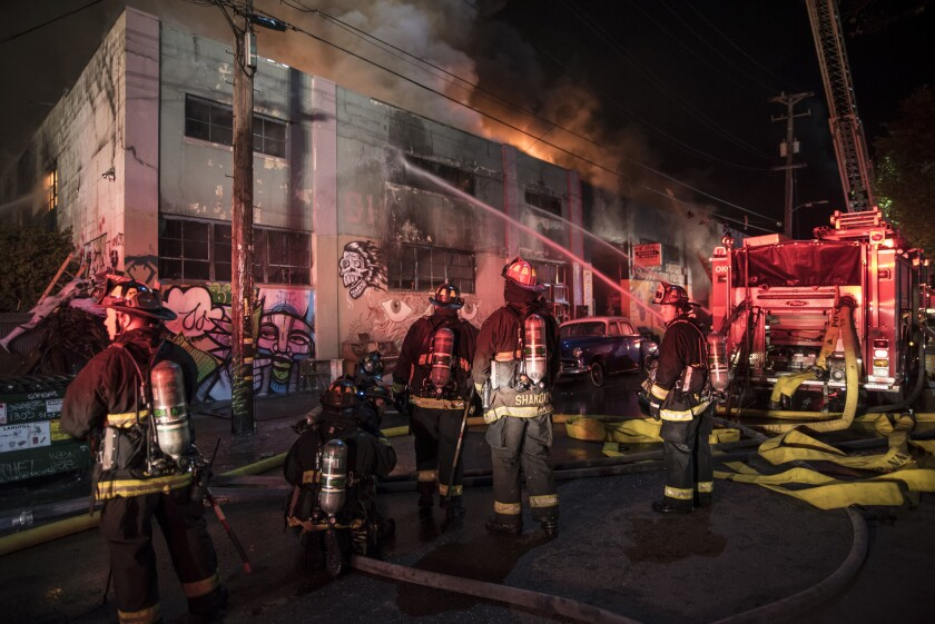 Firefighters battle the blaze that killed 36 people attending a concert at a warehouse in Oakland.