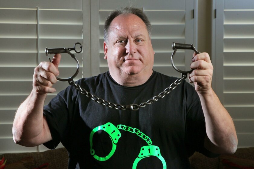 Mark Lyons of Encinitas holds a pair of Civil War-era handcuffs made by the Providence Tool Company. It's one of more than 1,000 pairs in his collection.
